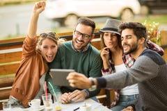 Groupe de quatre amis ayant un café ensemble Photographie stock libre de droits