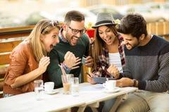 Groupe de quatre amis ayant un café ensemble Images libres de droits