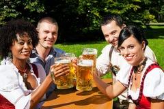 Groupe de quatre amis dans le jardin de bière Images libres de droits