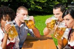 Groupe de quatre amis dans le jardin de bière Photographie stock libre de droits