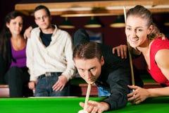 Groupe de quatre amis dans un hall de billard jouant s Image stock