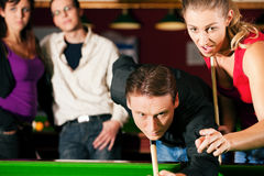 Groupe de quatre amis dans un hall de billard jouant s Photo stock
