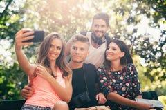 Groupe de quatre amis drôles prenant le selfie Image libre de droits