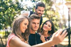 Groupe de quatre amis drôles prenant le selfie Photo stock