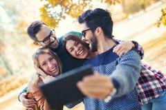 Groupe de quatre amis drôles prenant le selfie Photos stock