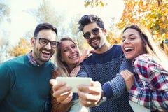 Groupe de quatre amis drôles prenant le selfie Image stock