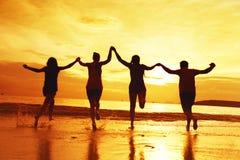 Groupe de quatre amis heureux à la plage de coucher du soleil Photographie stock libre de droits