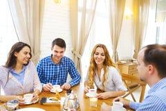 Groupe de quatre amis heureux rencontrant et parlant et mangeant le desse Image stock