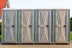 Groupe de quatre bio latrines sur la rue photo stock