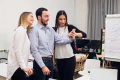 Groupe de quatre collègues gais divers prenant l'autoportrait et faisant des gestes drôles avec des mains au petit bureau Photographie stock libre de droits
