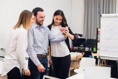 Groupe de quatre collègues gais divers prenant l'autoportrait et faisant des gestes drôles avec des mains au petit bureau Images stock