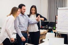 Groupe de quatre collègues gais divers prenant l'autoportrait et faisant des gestes drôles avec des mains au petit bureau Photo stock