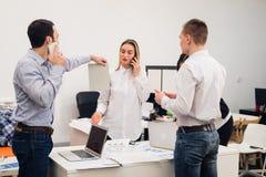 Groupe de quatre collègues gais divers prenant l'autoportrait et faisant des gestes drôles avec des mains au petit bureau Photos stock