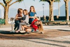 Groupe de quatre enfants ayant l'amusement sur le terrain de jeu Photographie stock