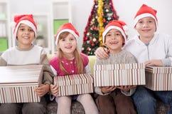 Groupe de quatre enfants dans le chapeau de Noël avec des présents Images libres de droits