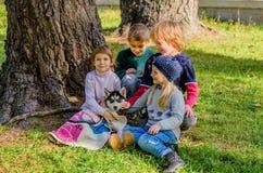 Groupe de quatre enfants jouant avec le chiot enroué en parc Image libre de droits