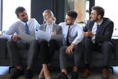 Groupe de quatre hommes d'affaires s'asseyant sur le sofa Ils n'ont pas pu ?tre plus heureux au sujet du travail ensemble images stock