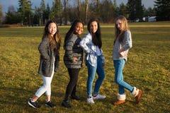 Groupe de quatre jeune amie se tenant et posant dehors Photo stock