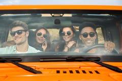 Groupe de quatre jeunes amis gais s'asseyant dans une voiture Photos stock