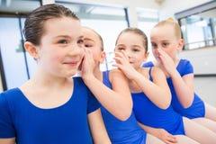 Groupe de quatre jeunes filles disant des secrets ensemble Images libres de droits