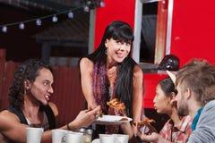 Quatre personnes heureuses mangeant de la pizza photos stock