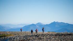 Groupe de quatre personnes marchant sur la montagne rocheuse platon Images stock