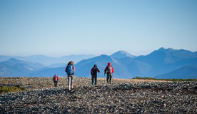 Groupe de quatre personnes marchant sur la montagne rocheuse platon Image libre de droits