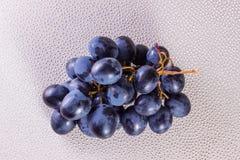 Groupe de raisins bleus sur un fond d'un conseil de plastique avec des boutons Image stock