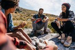 Groupe de randonneurs détendant dans le domaine Photographie stock