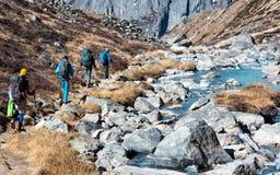 Groupe de randonneurs marchant sur le sentier piéton dans la vue arrière de montagnes Photos libres de droits