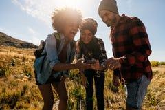 Groupe de randonneurs regardant des photos sur le téléphone et rire Images libres de droits