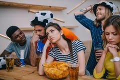 groupe de renversement d'amis multi-ethniques dans des chapeaux de ballon de football observant le match de football photographie stock libre de droits
