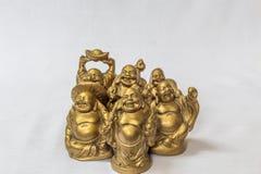 Groupe de rire Bouddha peint dans la couleur d'or dans un contexte blanc Macro avec la profondeur du champ extrêmement Photo stock
