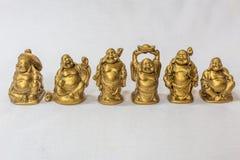 Groupe de rire Bouddha peint dans la couleur d'or dans un contexte blanc Macro avec la profondeur du champ extrêmement Image libre de droits