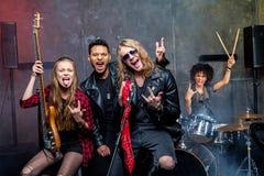Groupe de rock posant dans le studio Image stock