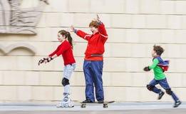 Groupe de rollerskating d'enfants en parc public Photographie stock