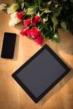 Groupe de roses avec le smartphone et le comprimé numérique sur la table en bois Photos libres de droits