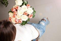 Groupe de roses chez des mains du ` s de la femme Photographie stock libre de droits