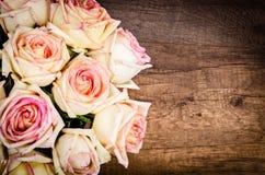Groupe de roses roses contre un mur en bois Images stock