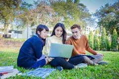 Groupe de séance asiatique d'étudiants sur l'herbe verte W Images stock
