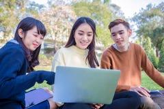 Groupe de séance asiatique d'étudiants sur l'herbe verte W Image libre de droits