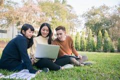 Groupe de séance asiatique d'étudiants sur l'herbe verte W photo stock