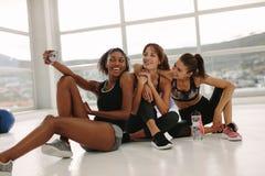 Groupe de selfie de prise femelle dans le gymnase Photos stock