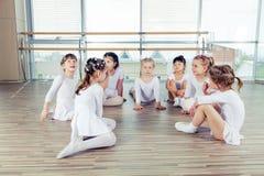 Groupe de sept petites ballerines s'asseyant sur le plancher Ils sont Photos libres de droits