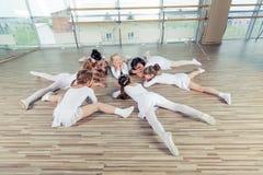 Groupe de sept petites ballerines s'asseyant sur le plancher Ils sont bon ami et interprètes étonnants de danse Images stock