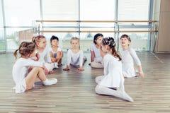 Groupe de sept petites ballerines s'asseyant sur le plancher Ils sont bon ami et interprètes étonnants de danse Photos stock
