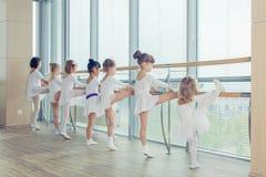Groupe de sept petites ballerines se tenant dans la rangée et la pratique Photo stock
