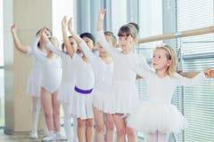 Groupe de sept petites ballerines se tenant dans la rangée et la pratique Image libre de droits