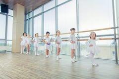 Groupe de sept petites ballerines se tenant dans la rangée et la pratique Photo libre de droits