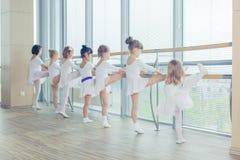 Groupe de sept petites ballerines se tenant dans la rangée et la pratique Photos stock